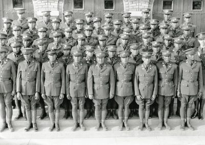 1930 black and white photo of young Native men in military uniforms posing on steps