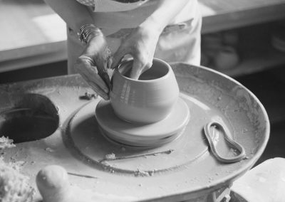 1940s black and white photo detail of pottery being shaped on a pottery wheel