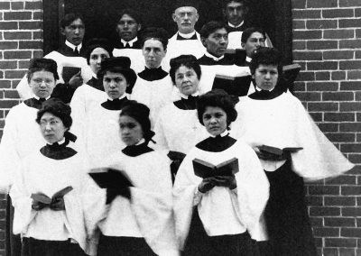 1902 black and white photo of young Native women and men in ecclesiastical choir outfits holding hymnals posed on steps at arched building entrance. An older Caucasian male clergy stands with them at the back.