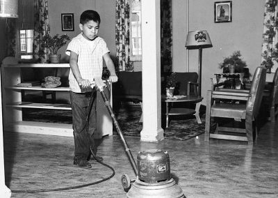 1950 black and white photo of a young Native boy polishing a floor with a waxing machine in a domestic setting.