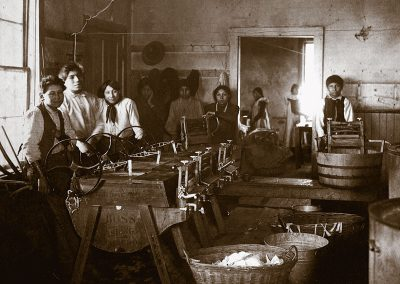 1890 black and white photo of Native youth in laundry room with manual equipment for doing laundryunderneath