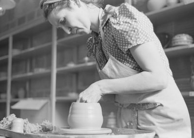 1940s black and white photo of young woman shaping a vessel on a pottery wheel with shelves of pottery behind her.