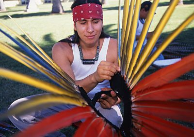1999 candid color photo of a young Native man wearing a red bandana around his forehead and carefully aligning long feathers on a head dress