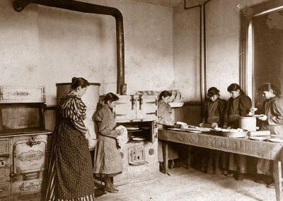 1900 black and white photo of an older woman with several young Native girls baking in a kitchen