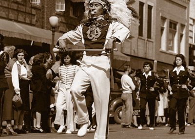1940 black and white photo of a male drum major in marching costume with headress carrying a twirling batton in both hands and a whistle in his mouth. He marches down the middle of a street in front of the rest of the band with bystanders looking on.
