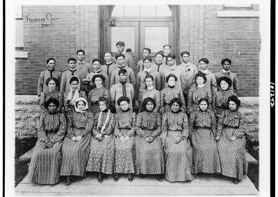 1900 black and white photo of young Native men and women in period dresses and military style uniforms posing in front of a brick building.