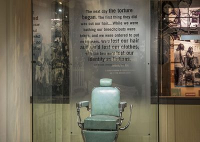 Old style barber chair with metal arms and smooth teal blue leather like materal enclosed in a large glass case. Black braids and cut hair lay around the chair on the floor.