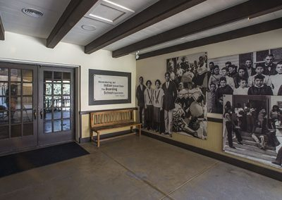 Covered porch entry with photographic images of Native American youth on the walls.