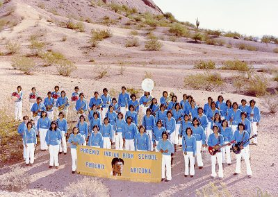 "1982 color photo of Native youth band members in blue velvet tunics tied at the waist with concho belts and white trousers. All are holding their instruments and a yellow banner which says ""Phoenix Indian High School, Phoenix, Arizona."" They stand in a desert setting."