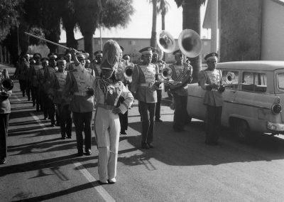 1960 black and white photo of a marching band on the road with a drum major in front with her baton raised and whistle in her mouth.