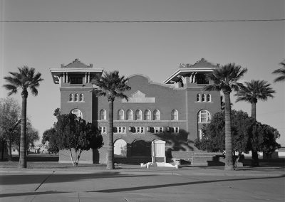 Black and white photo of a 3 story brick building with a mission-style facade and towers on both front corners.