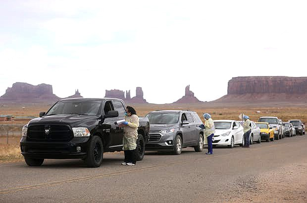 cars lined up on a desert road with Monument Valley in the background while medical personal stand at each driver window