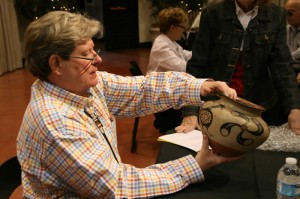 Photograph of appraiser Alston Neal examining a basket during a recent Appraisal Day