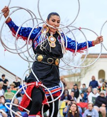 American Indian hoop dancer, Lisa Odjig, performing at the World Championship Hoop Dance Contest at the Heard Museum in front of a filled amphitheater of spectators.