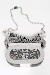 Sterling Silver Hand Bag by Native Jeweler's Society: Featuring the work of Darryl Dean Begay, Phil Begay, Gene Billie, Ric Charlie, Tim Herrera, Ray Scott and Roy Tenorio Inlaid coral and turquoise with magnetic clasp for closing Purse value: $20,000