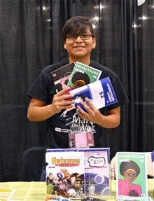 Photograph of Damon Begay holding three comic books