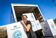 Photograph of woman holding a Food Drive box, with a truck filled with Food Drive boxes in the background.