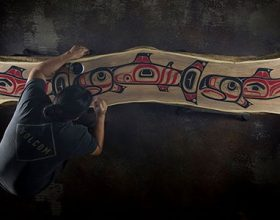 Tlingit artist James Johnson, seen from above with his back to the camera as he works on a half sawn log decorated with Nortwest Coast fish designs in red and black