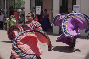 Young girls weraing colorful skirts dancing Folklorico in the plaza during event, Dia Del Nino.