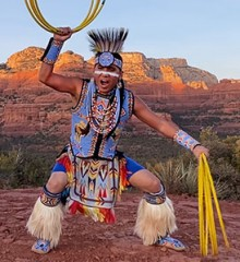 Native American hoop dancer Tony Duncan in traditional regalia and with his hoops striking a dramatic pose against the backdrop of the mountains of the desert southwest