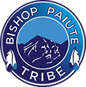 """Blue circle logo with mountains in the center and """"Bishop Paiute Tribe"""" circling inside of logo."""