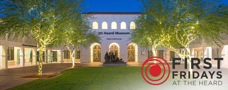 night scene of the Steel Auditorium facade as seen from the end of the grass and pavemented courtyard lined with string-light wrapped Palo Verde trees