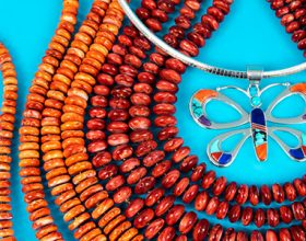Layered bright orange strands of spiny oyster and a silver wire butterfly shaped pendant over a turquoise colored background.