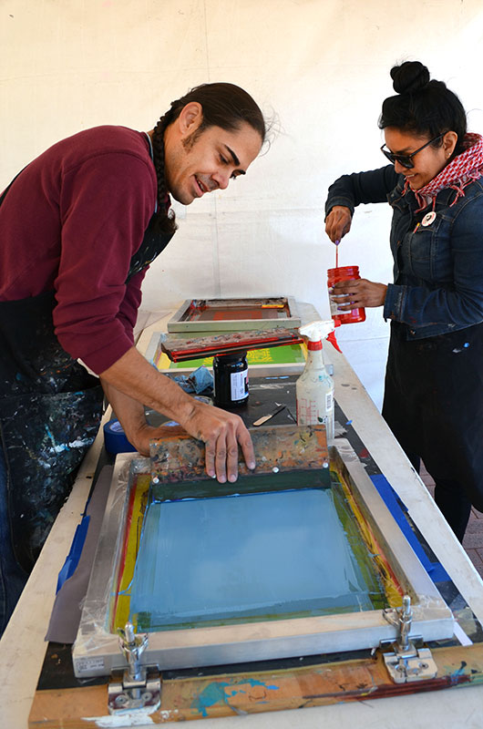 Artists Jacob Meders and Melissa Cody in a white tent in front of a table with screen printing tools