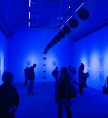 blue-lit high-ceiling room with speakers suspended through the middle and people walking around