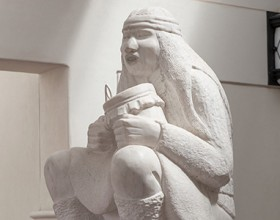 Sculpture by Allan Houser titled Earth Song showing an older Native American man seated with a small drum in traditional dress with mouth open as if singing carved from white marble