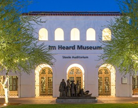 First Friday event banner showing the exterior of Steele Auditorium at dusk with the grassy courtyard, ringed by light wrapped Palo Verde trees