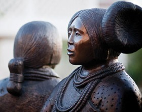 Detail of Doug Hyde's bronze sculpture Intertribal Greeting showing Native American women from different tribes of the southwest in traditional dress gathered together