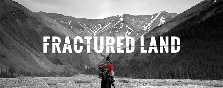 Man's back is turned standing in front of a black and white landscape with mountains.