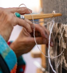 Close up of woman's hands weaving on a loom.