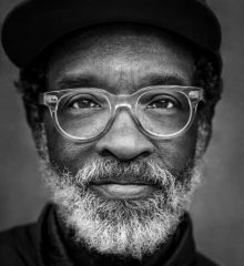 closeup portrait of older African American man with grey beard, horn-rim style glasses and cap