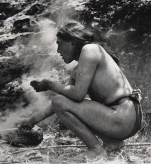 A black and white photograph of Ishi squatting and making a fire.