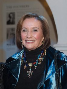 Smiling woman with shoulder length light brown hair with elaborate necklace
