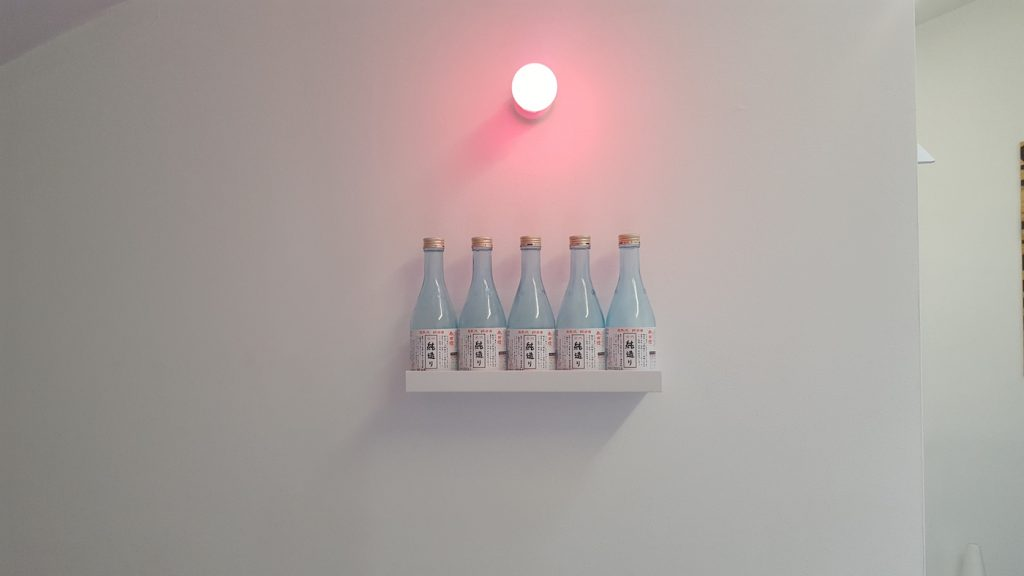 "Maria Hupfield and Jason Lujan, ""Drink Bar for Two."" Five sake bottles, wooden shelf, pink lightbulb. Collection of the artists"