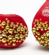 Photo of red boxing gloves sprinkled with gold colored metal balls