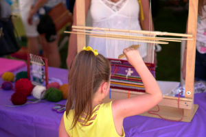 Young girl wearing yellow using small loom to weave a rug with artist Velma Craig (Dine)