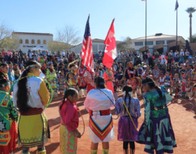 Native American Hoop dancers in traditional regalia gathered around a circular sand dance plaza with the US and Canadian flags held in the center