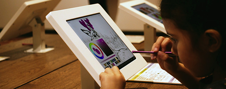 Small child coloring on an iPad mounted to a wooden table