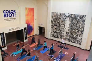 Group of yoga students practicing yoga in museum gallery.