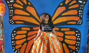 Young woman stands in front of butterfly mural.