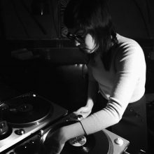 Young woman spins vinyl record in black and white image.