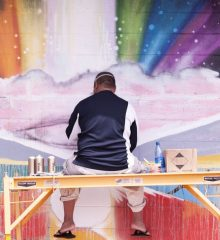 man sits on scaffold spray painting rainbows coming out of clouds.