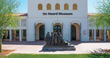 white plaster arched walkway fronted building with brick pavers and bronze sculpture of American Indian women of the southwest in front