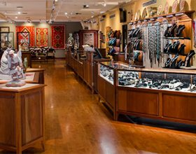 Native American art gallery with dark wooden floors and cases showing Native rugs, jewelry, other art