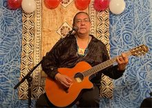 older Native American man sitting playing a guitar in front of a wall covered in highly textured cloth and red and white balloons