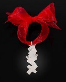 flat silver ornament of geometric zigzags with bright red ribbon